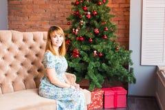Mujer joven que se sienta en el sofá cerca de un árbol de navidad con las cajas de regalo Año Nuevo y concepto de la Navidad Fotografía de archivo