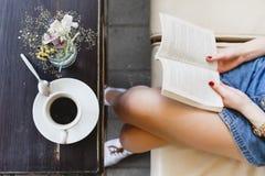 Mujer joven que se sienta en el sofá de cuero y que sostiene un libro Foto de archivo