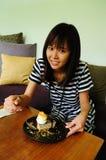 Mujer joven que se sienta en el sofá en un café que come la torta Fotografía de archivo