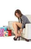 Mujer joven que se sienta en el sofá que saca sus zapatos Fotos de archivo