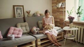Mujer joven que se sienta en el sofá y el suéter de lana que hace punto almacen de video