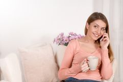 Mujer joven que se sienta en el sofá y el té o el café de consumición foto de archivo