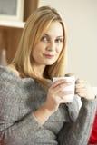 Mujer joven que se sienta en el sofá con la taza de café Fotografía de archivo