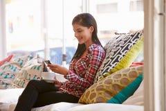 Mujer joven que se sienta en el sofá en un café Imagen de archivo