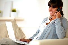 Mujer joven que se sienta en el sofá que habla en el teléfono móvil Imagen de archivo libre de regalías