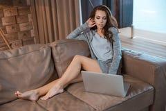 Mujer joven que se sienta en el sofá y el concentrado usando el ordenador portátil Foto de archivo