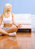 Mujer joven que se sienta en el suelo de madera Meditating Fotografía de archivo