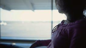 Mujer joven que se sienta en el terminal de aeropuerto, para vuelo que espera, encontrando a parientes almacen de video