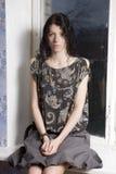 Mujer joven que se sienta en el windowsill fotografía de archivo libre de regalías