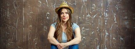 Mujer joven que se sienta en fondo marrón del grunge Fotografía de archivo