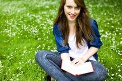 Mujer joven que se sienta en hierba Imagenes de archivo