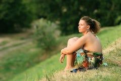 Mujer joven que se sienta en hierba Imágenes de archivo libres de regalías