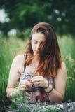 Mujer joven que se sienta en hierba Fotografía de archivo libre de regalías