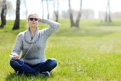Mujer joven que se sienta en hierba en el parque que selecciona música en smartpho Foto de archivo