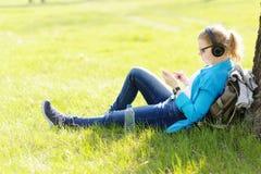Mujer joven que se sienta en hierba en el parque que selecciona música en smartpho Imagenes de archivo