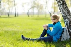 Mujer joven que se sienta en hierba en el parque que selecciona música en smartpho Fotos de archivo libres de regalías