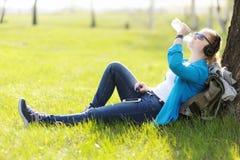 Mujer joven que se sienta en hierba en el parque que selecciona música en smartpho Foto de archivo libre de regalías