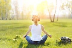 Mujer joven que se sienta en hierba en parque y el meditar y listenin Fotografía de archivo