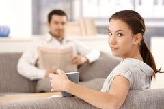 Mujer joven que se sienta en hombre del sofá en fondo Foto de archivo libre de regalías
