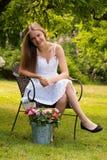 Mujer joven que se sienta en jardín con las flores Imágenes de archivo libres de regalías