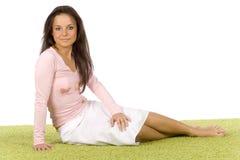 Mujer joven que se sienta en la alfombra verde Imagen de archivo libre de regalías