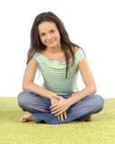 Mujer joven que se sienta en la alfombra verde Foto de archivo libre de regalías