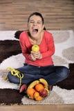 Mujer joven que se sienta en la alfombra y que goza de las frutas fotos de archivo
