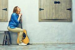 Mujer joven que se sienta en la calle con la guitarra Imagenes de archivo