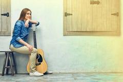 Mujer joven que se sienta en la calle con la guitarra Fotografía de archivo