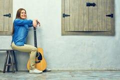 Mujer joven que se sienta en la calle con la guitarra Imagen de archivo