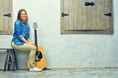 Mujer joven que se sienta en la calle con la guitarra Fotos de archivo libres de regalías