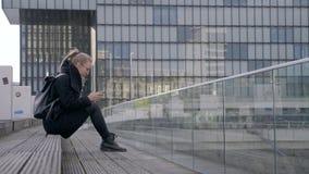 Mujer joven que se sienta en la calle almacen de video