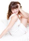 Mujer joven que se sienta en la cama blanca Imagen de archivo libre de regalías