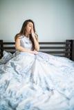 Mujer joven que se sienta en la cama y que bosteza en casa Fotografía de archivo