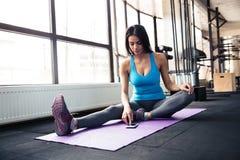Mujer joven que se sienta en la estera de la yoga y que usa smartphone Imagen de archivo libre de regalías