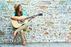 Mujer joven que se sienta en la guitarra del juego de la silla Foto de archivo libre de regalías
