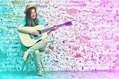 Mujer joven que se sienta en la guitarra del juego de la silla Imagen de archivo