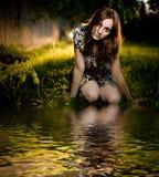 Mujer joven que se sienta en la hierba Imágenes de archivo libres de regalías