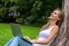 Mujer joven que se sienta en la hierba con el ordenador portátil Fotografía de archivo