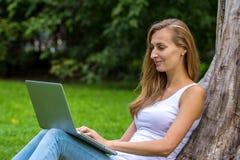 Mujer joven que se sienta en la hierba con el ordenador portátil Fotos de archivo