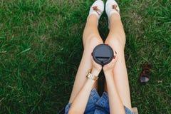 Mujer joven que se sienta en la hierba con la taza de café Foto de archivo