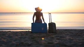 Mujer joven que se sienta en la maleta en una playa almacen de metraje de vídeo