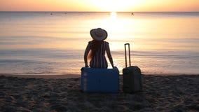 Mujer joven que se sienta en la maleta en una playa almacen de video