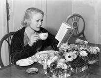 Mujer joven que se sienta en la mesa de comedor que sostiene una taza de té y que lee un libro (todas las personas representadas  fotos de archivo