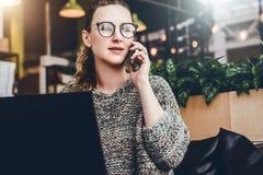 Mujer joven que se sienta en la oficina, café en la tabla delante del ordenador portátil y hablando en el teléfono móvil El Freel fotografía de archivo libre de regalías