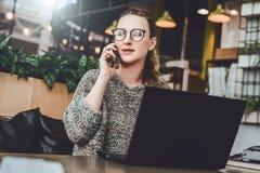 Mujer joven que se sienta en la oficina, café en la tabla delante del ordenador portátil y hablando en el teléfono móvil El Freel foto de archivo