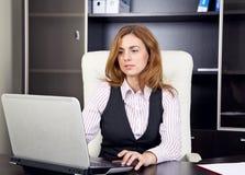 Mujer joven que se sienta en la oficina que mecanografía en el ordenador portátil Foto de archivo