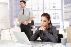 Mujer joven que se sienta en la oficina que mira el ordenador portátil imagen de archivo