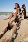 Mujer joven que se sienta en la playa Foto de archivo