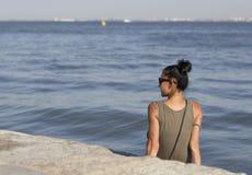 Mujer joven que se sienta en la playa Fotos de archivo libres de regalías